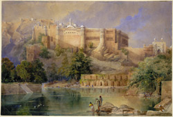 The Fort at Amber, Rajasthan, showing part of the Raj Mahal from the opposite bank of the Maota Lake, and low arched buildings used as elephant stables at the water's edge